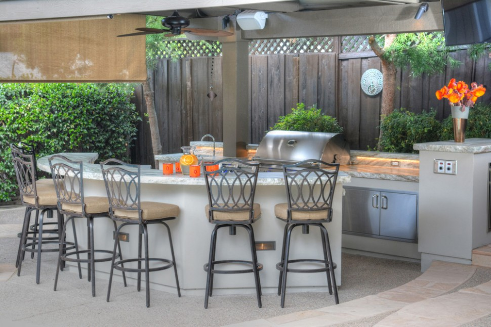 The curved edge of the bar countertop creates seating for 8 in Alamo, CA outdoor kitchen and living space remodel