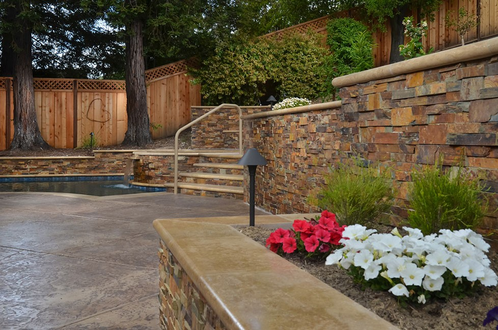 Custom stone walls and patio in outdoor kitchen design project in Alamo, CA.