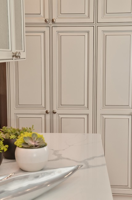 Overlay cabinets in a striking white with gray glazing