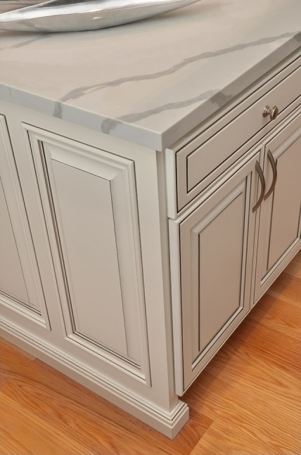 Cabinets are done in a striking white with gray glazing