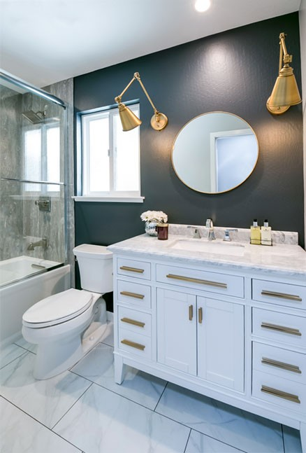 A round antique brass mirror, with articulating arm wall sconces, finish off this bathroom beautifully.