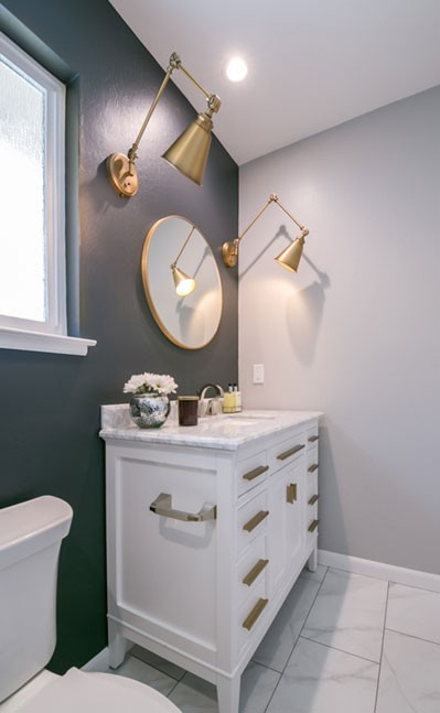 The white vanity is topped with a marble counter and accented with antique hardware.