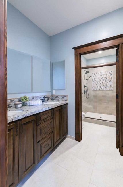 This remodeled bathroom includes Natural Quartz 'Antico Cloud' countertops.