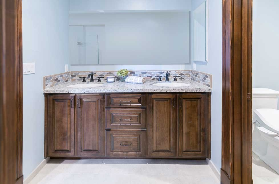 The double vanity has raised panel cabinetry in Clear Alder in a New World finish with an accent glaze.