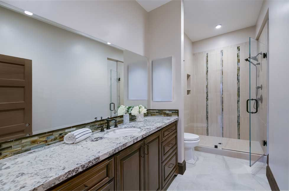 This remodeled bathroom includes Alder cabinetry and a Quartz countertop.