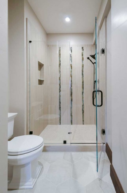 The renovated oversize shower includes contemporary 1x4 brick 'Tozen' vertical accent tile in copper natural.