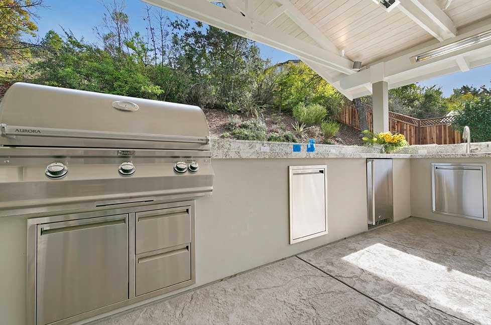 The outdoor kitchen includes a large BBQ, stainless steel refrigerator and undermount sink.