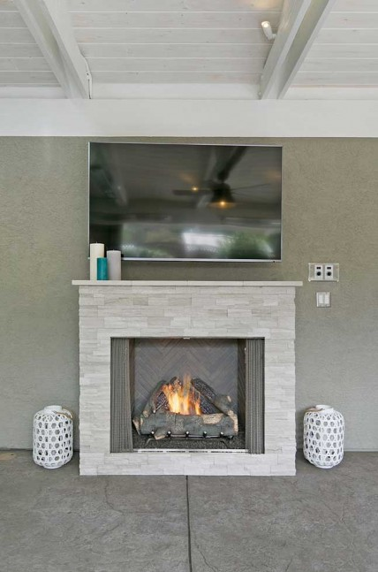 The outdoor gas fireplace is made of beautiful white stacked stone with a stone mantel.