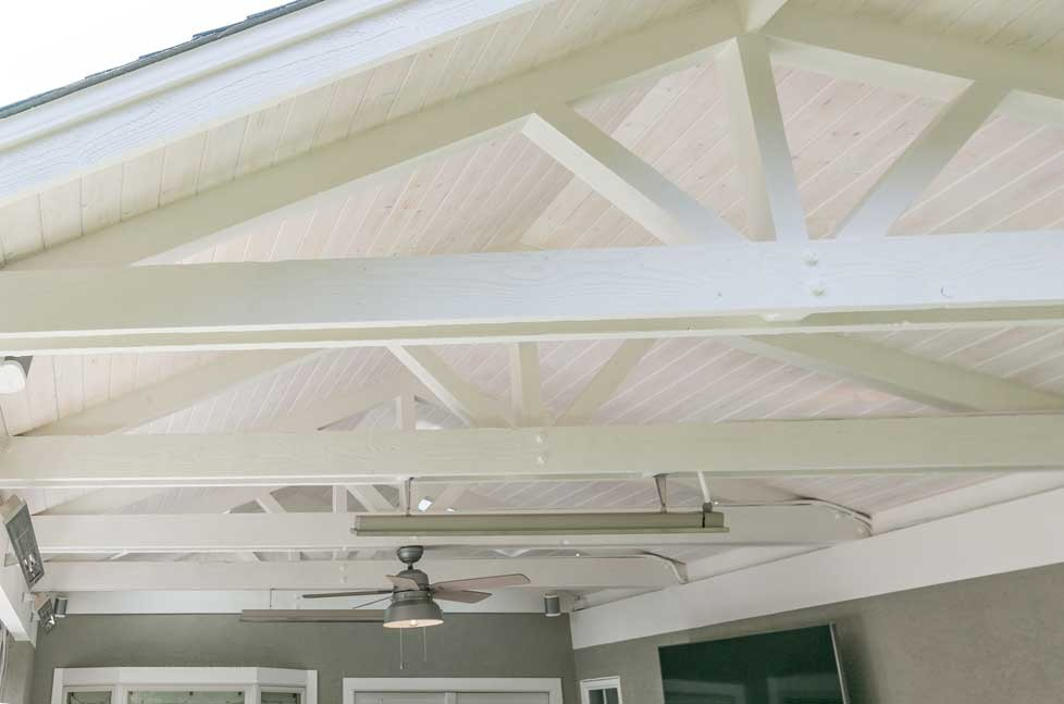The outdoor pavilion is finished with a whitewash open beam ceiling and a skylight.